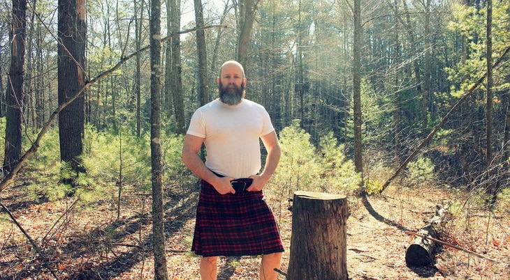 A man with a beard is wearing a kilt in the forest