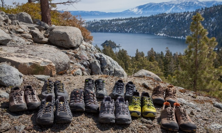 A lot of pair of hiking boots and a landscape in the background