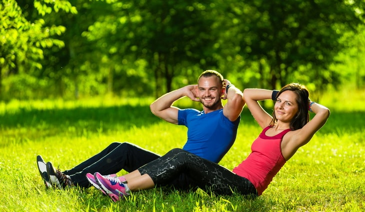 two adults doing sit ups exercises outside on the grass