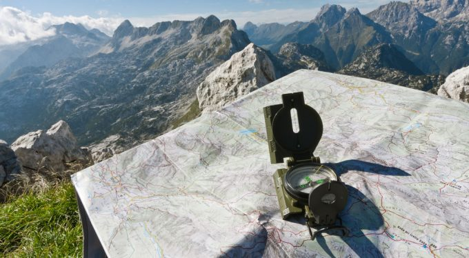 Image showing a compass on a map and a moutain landscape