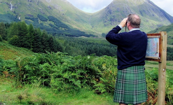 A man with a kilt is looking at the moutains landscape