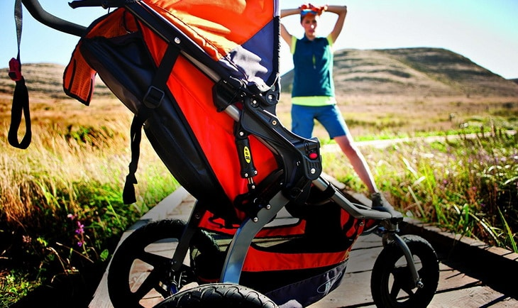Image of a woman in front of a hiking stroller