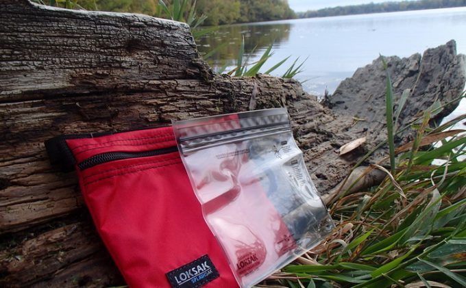 Image of Image showing Loksak Opsak waterproof bags on the ground near a water