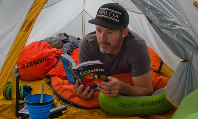 A-man-sitting-in-a-sea-to-summit-sleeping-bag-liner-and-reading-a-book