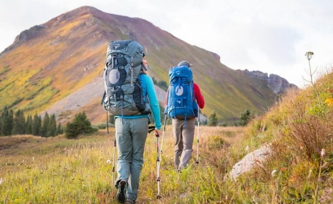 Two adults carring two backpacks while hiking