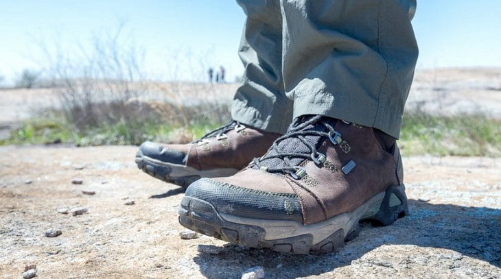 Close up photo of a man's legs wearing hiking boots