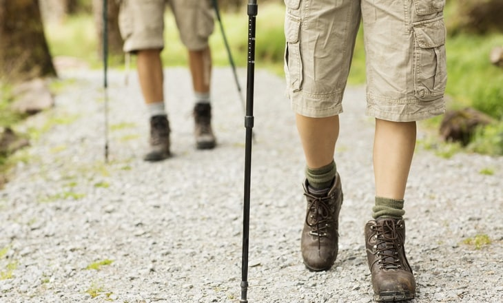 Low section of male and female hikers walking in shorts with trekking poles