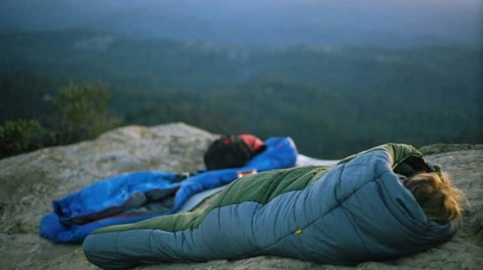 Image showing a woman sitting in a sleeping bag outside