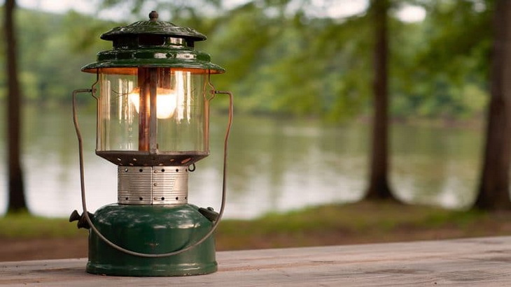 IImage showing a gas camping-lantern and a forest view