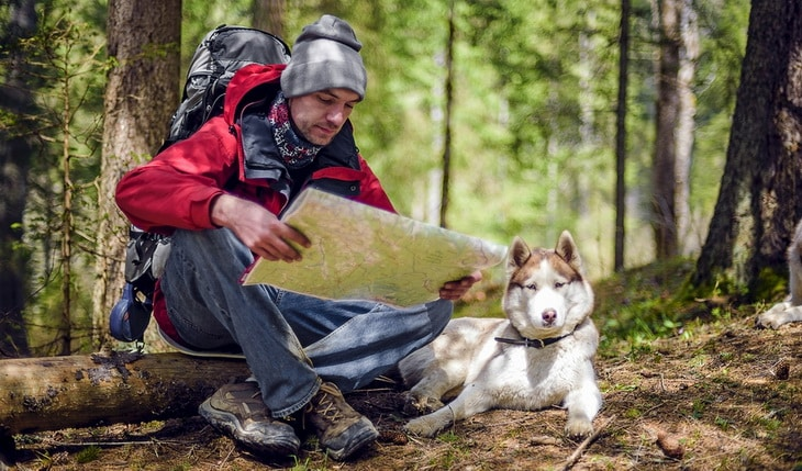 A man hiking in the forest with his dog