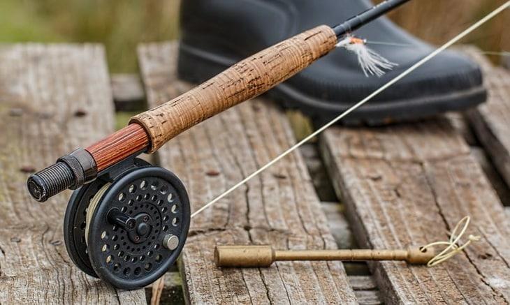Image of a fishing-rod near a man's legs