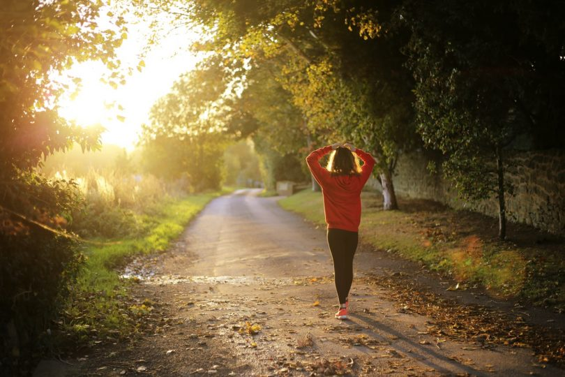 Girl Wearing Orange Long Sleeve Shirt and Black Pants Walking Alone Along Road Facing the Sun (2)