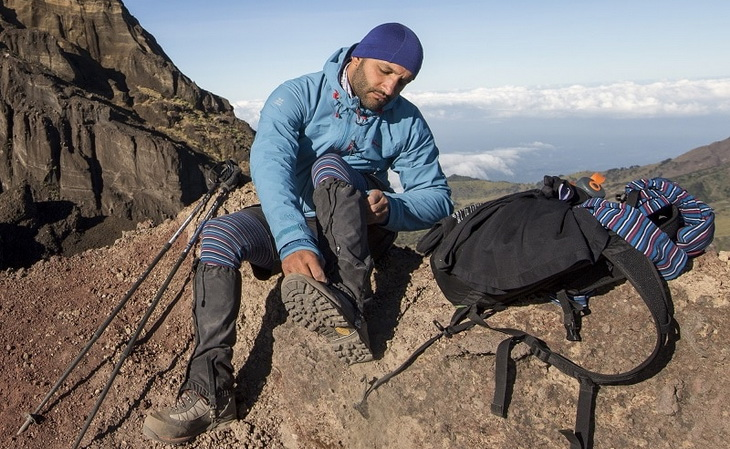 Hiker on top of the moutains looking at his gaiters