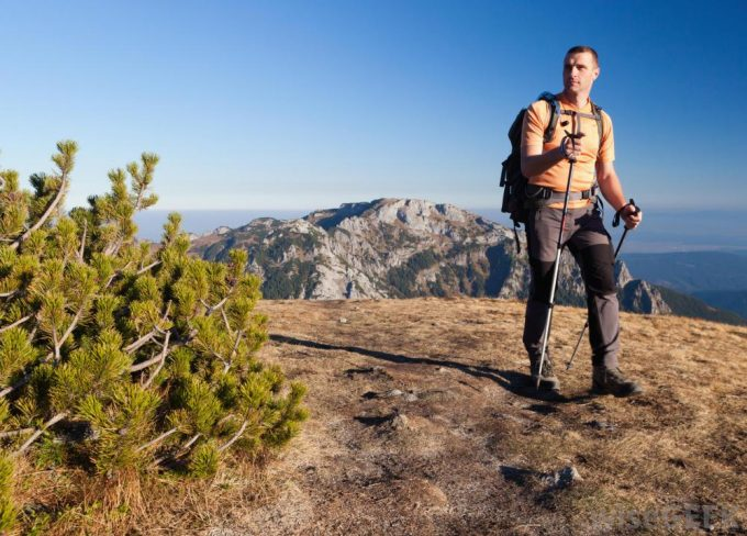 A man wering a pair of hiking pants made of synthetic materials may resist tearing and moisture from rain.