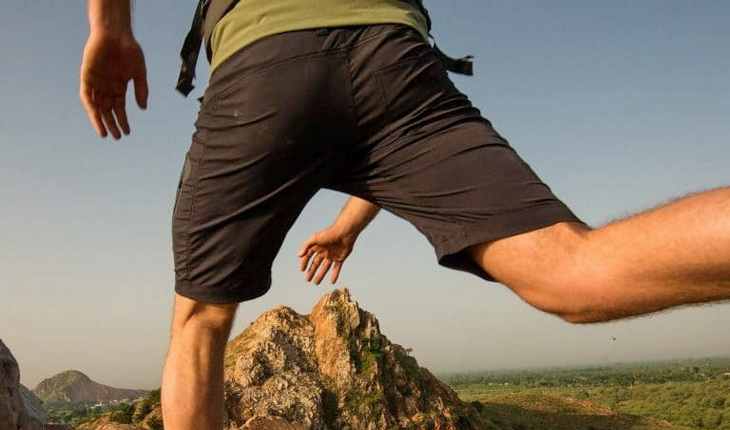 Image of a man jumping while wearing a pair of hiking shorts