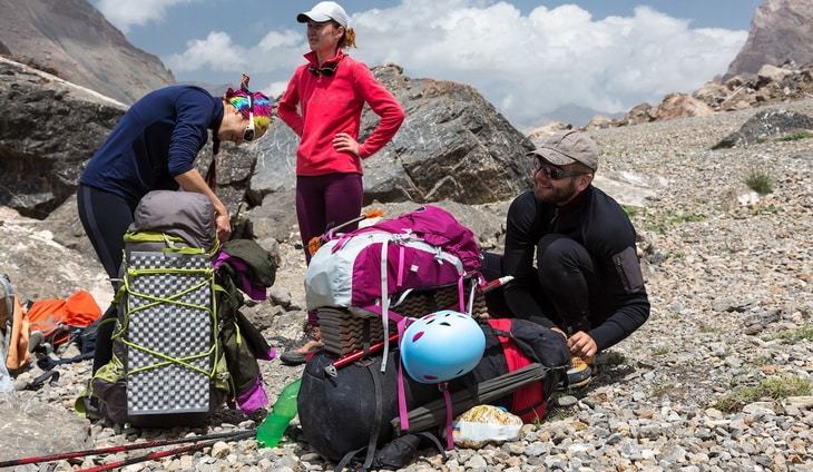 Group of People Man and Women Staying Along with Large Bags with Climbing Gear Attached such as Helmet Camping Mat Walking Poles Ice Axe