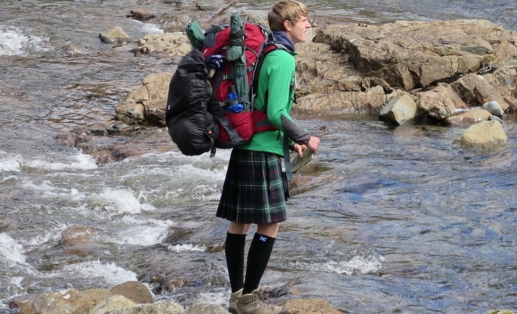 A man with a backpack and wearing a kilt trying to pass the river