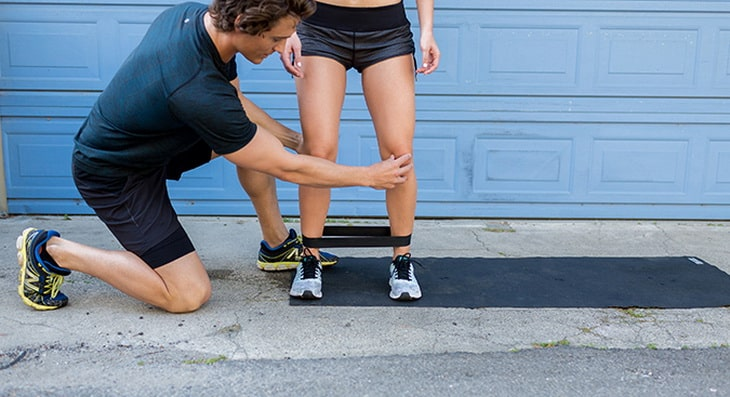 man showing a woman how to exercise with band walks