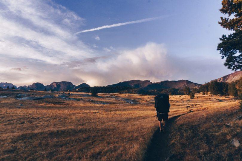 Man Walking Wearing Black Backpack during Daytime