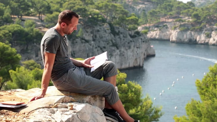 Man reading book on cliff in beautiful nature scenery