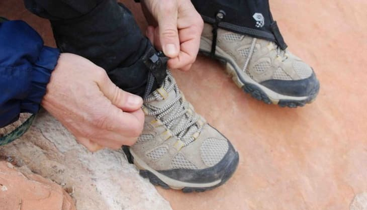 A man adjusting his gaiters