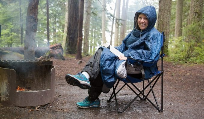 Woman near a camp fire is wearing a blue poncho