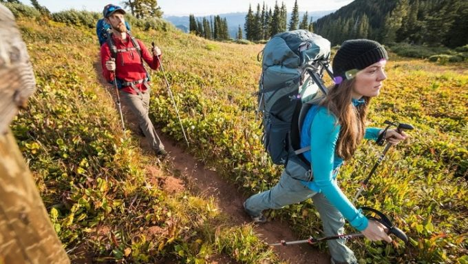 Image of two hikers with backpacks on a moutain road