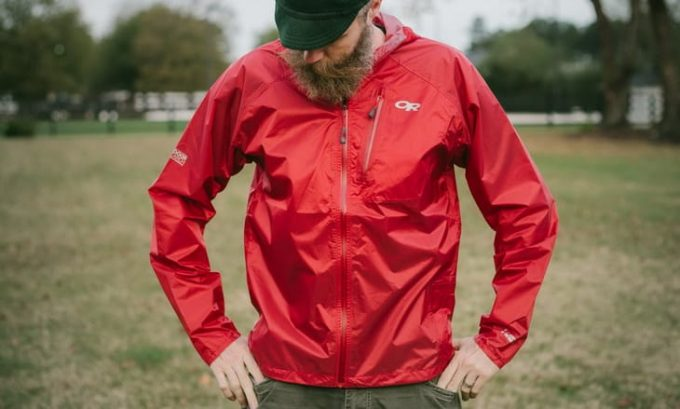 A man looking at his Outdoor-Research-Helium-II-Ultralight-Rain-Jackets-for-bike-touring-and-bikepacking