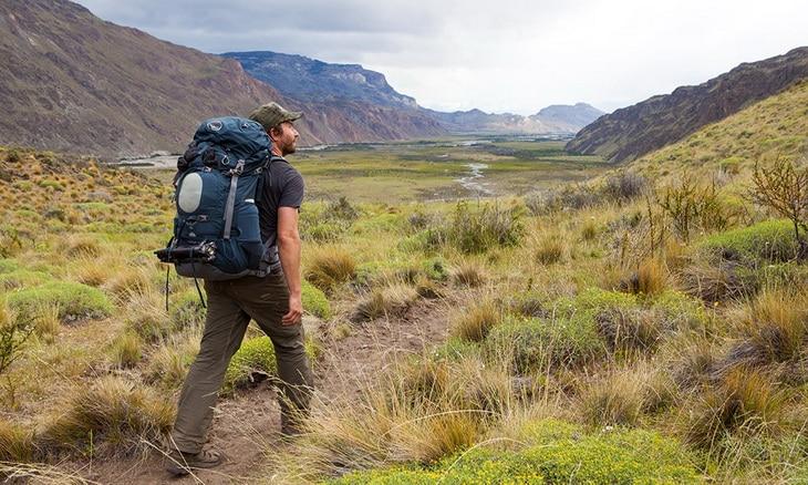 Backpacker walking and admiring landscape