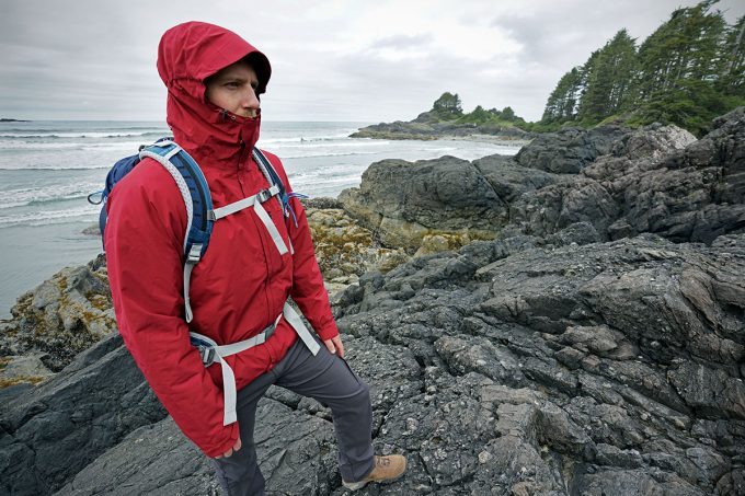 A man wearing a rain jacket and a pair of hiking pants on a trip