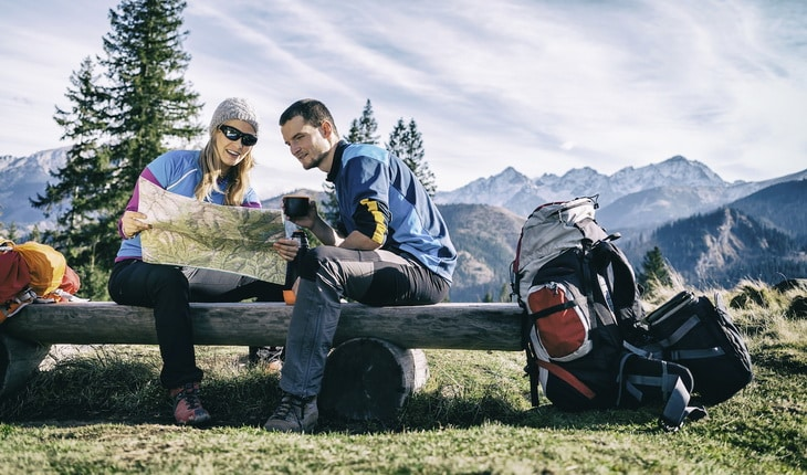 Couple hikers with map in mountains