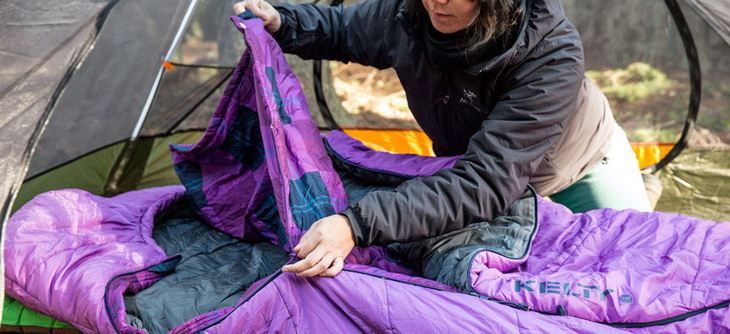 a camper carefully using their sleeping bag zipper