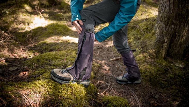 a-hiker-adjusting-their-gaiters-to-fit-properly