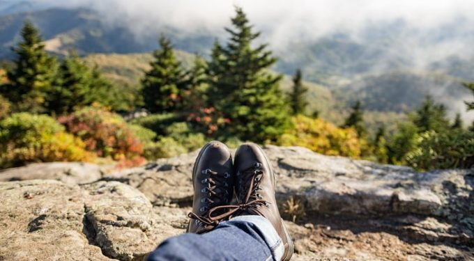 Image showing a man laying back on the ground and looking at the landscape