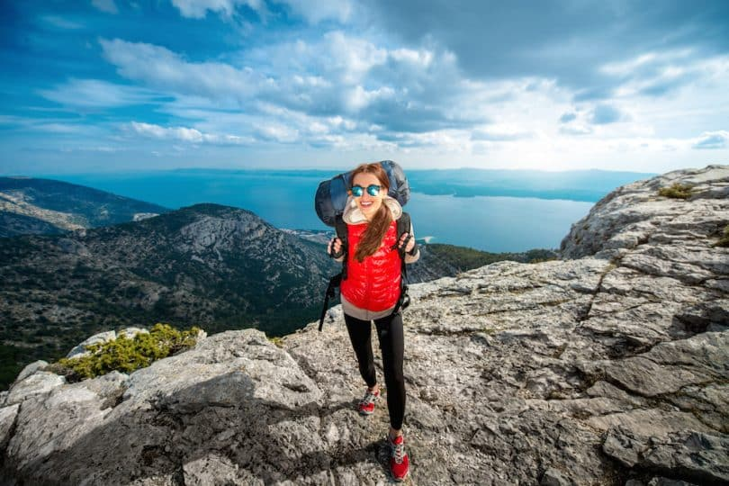 A woman with a backpack and wearing leggins is on top of the moutains