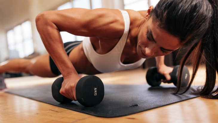 Strong young woman doing push ups exercise with dumbbells