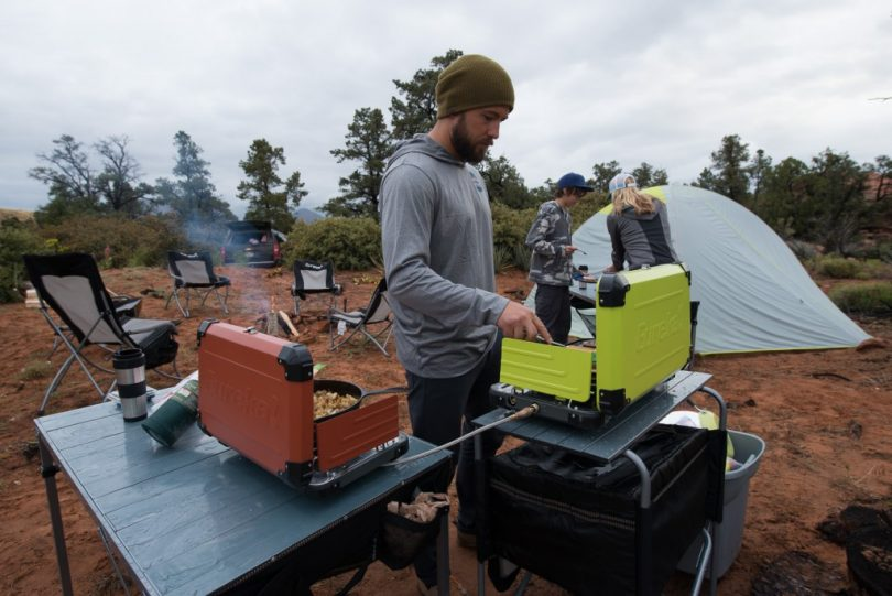 picture of a man cooking with a camp stove