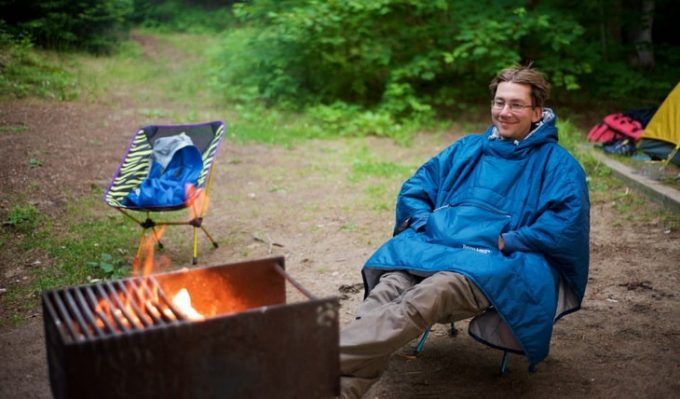 Man wearing a blue poncho is sitting on a chair near a camp fire