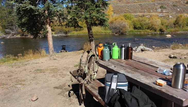 A couple of outdoor beer growler on a wooden table and a river in the background