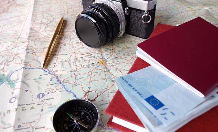 A camera, a compass, agenda and a pen on a map