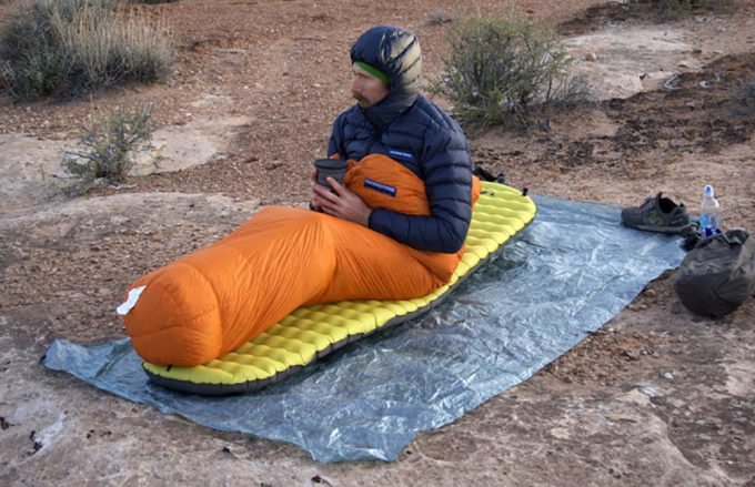 A man in a sleeping bag holding a cup of hot coffee