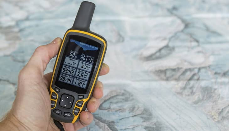 Hand held outdoor GPS and a hiking map of a mountain range.