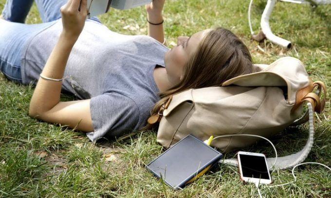 a woman relaxing on the grass reading a book