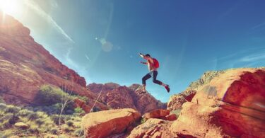 A man jumping from a rock to another