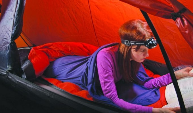 A woman in a sleeping bag in a tent reading a book in the night