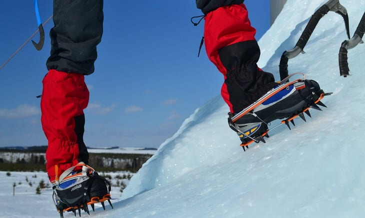 A man wearing Mountaineering Boots while climbing the ice