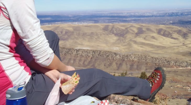 A woman wearing a hiking pants relaxing on top of the moutain