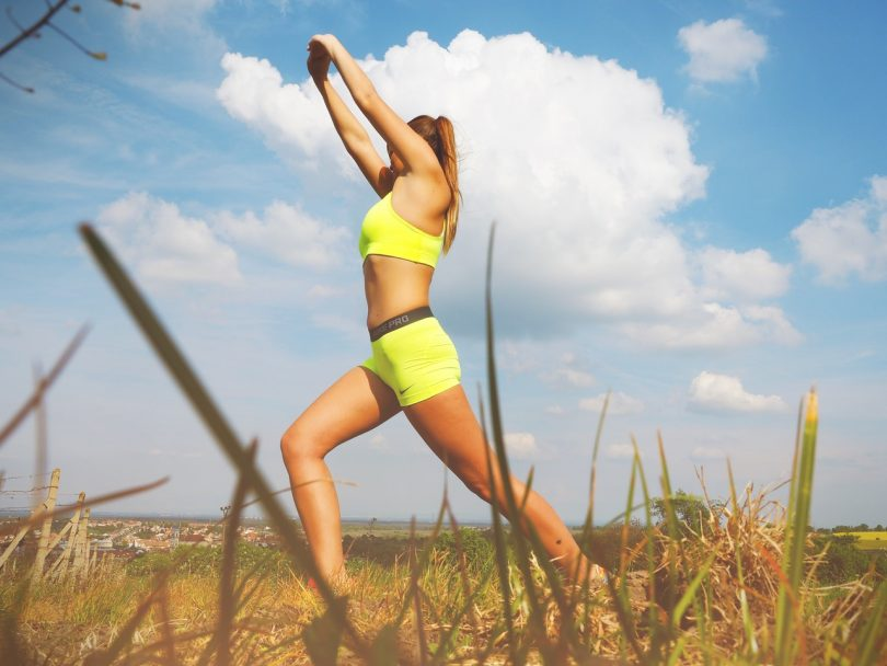 Woman in Yellow Sports Bra Stretching Near Green Grass Field