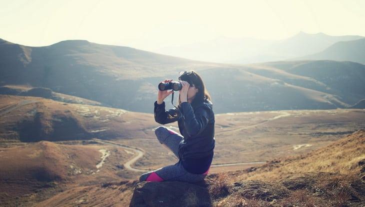 Woman Wearing Black Jacket Using Binoculars Sitting on Mountain
