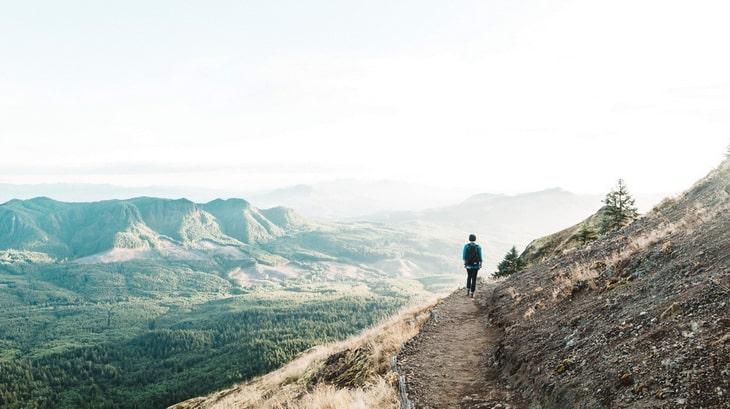 Man Walking on Cliff during Daytime